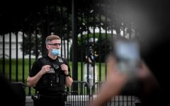 Armed Secret Service officers stand outside of the White House gate