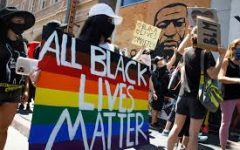 All Black Lives Matter protesters hold rainbow-colored signs near a mural of George Floyd during their solidarity march with the LGBTQ community in Los Angeles.